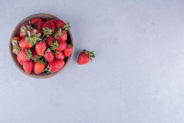 Aardbeien opgestapeld in een houten kom op marmeren achtergrond. hoge kwaliteit foto