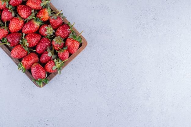 Aardbeien opgesteld in een klein dienblad op marmeren achtergrond. hoge kwaliteit foto