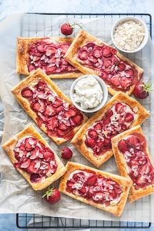 Aardbeien, roomkaas en amandel bladerdeeg taarten op bakpapier. blauwe betonnen achtergrond. bovenaanzicht.