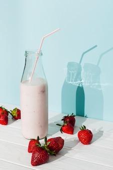 Aardbeien roze smoothie in glazen fles