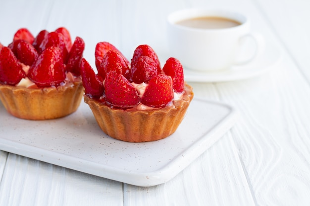 Aardbeien shortcake pasteitjestartlets met vla op witte houten achtergrond