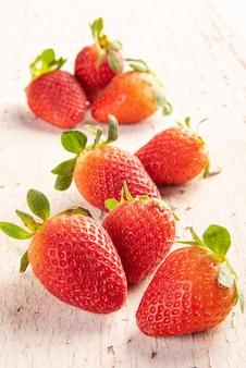 Aardbeien, verschillende mooie aardbeien op een oude en verweerde houten plank, selectieve aandacht.