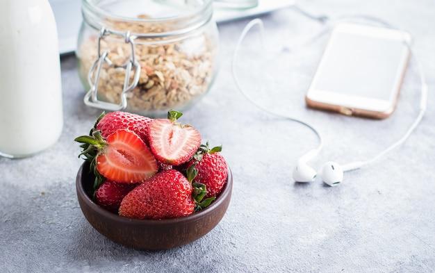 Aardbeien, yoghurt fles en granola pot, laptop en koptelefoon op lichte stenen tafel achtergrond.