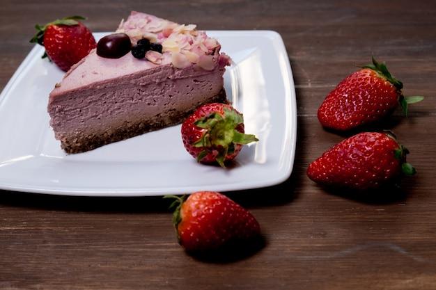 Aardbeiencheesecake op zwarte plaat over rustieke houten achtergrond. bovenaanzicht.