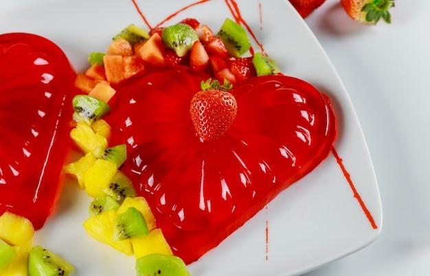Aardbeiengelatine versierd met verse aardbeien, kiwi en ananas.