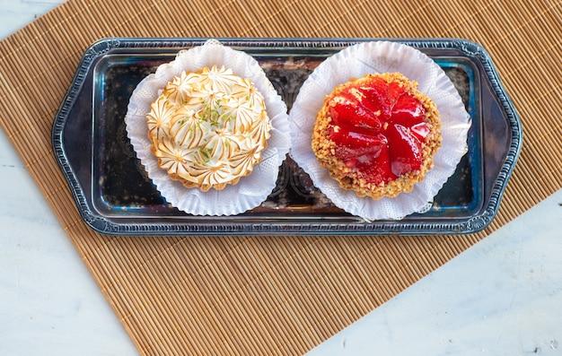 Aardbeienjam en citroenjam met natuurlijk licht op een dienblad, boven hout op een witte tafel, bovenaanzicht.