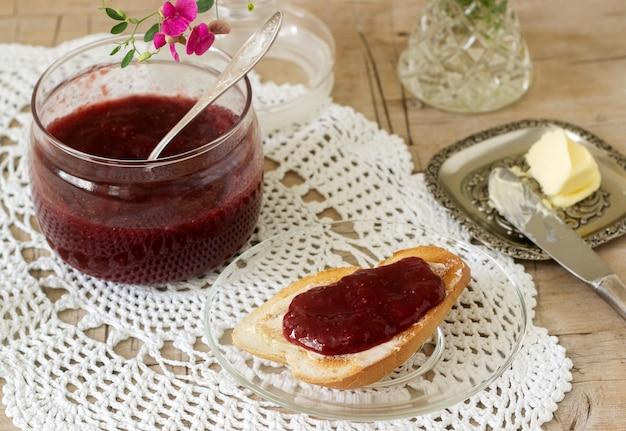 Aardbeienjam in een glazen pot en toast met boter en jam. rustieke stijl.