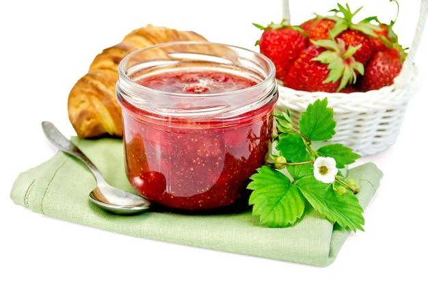 Aardbeienjam in een glazen pot, gelaagd broodje, aardbei, servet, lepel geïsoleerd op een witte achtergrond