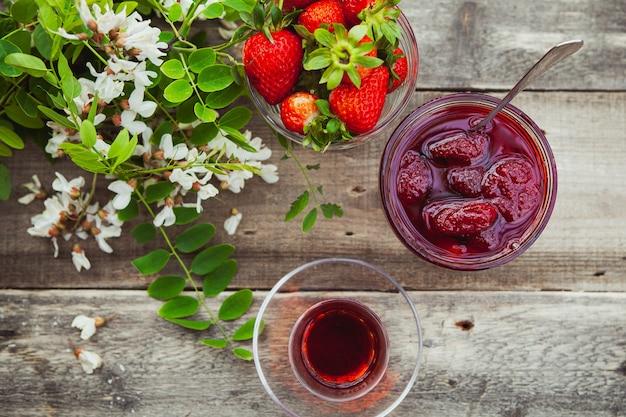 Aardbeienjam met lepel, een glas thee, aardbeien, plant in een plaat op houten tafel, bovenaanzicht.
