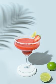 Aardbeienmargarita-cocktail met limoen en ijsblokje op blauwe achtergrond