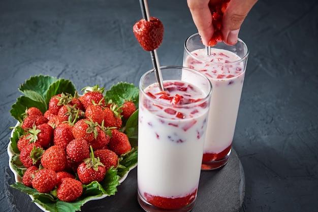 Aardbeienmelk smoothie in glas met stro en verse bessen op donkere achtergrond