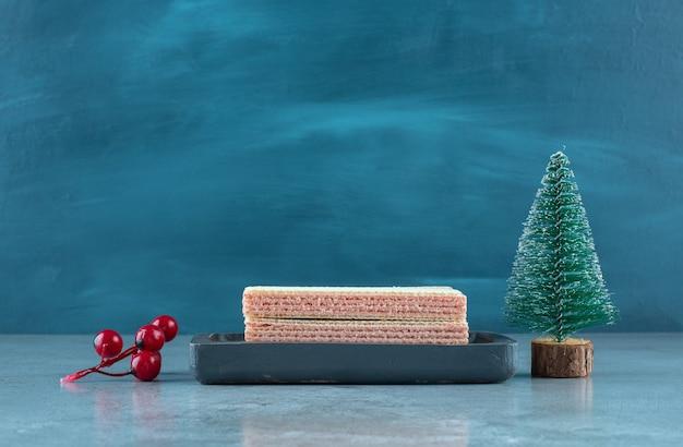 Aardbeienroom gevulde wafeltjes in een kleine bak naast kerstversieringen op marmeren oppervlak