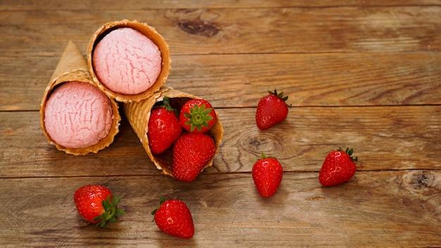 Aardbeienroomijs in een wafelkegel. rode bessen en ijsballen op een houten ondergrond.