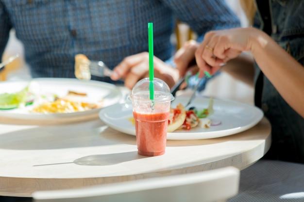 Aardbeiensap ligt op tafel terwijl mensen aan het ontbijten zijn