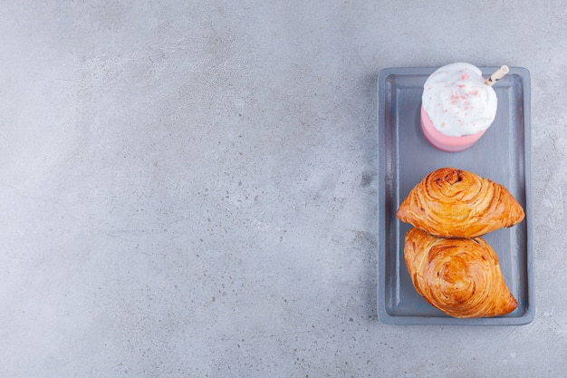 Aardbeiensmoothie met twee verse gebakjes op stenen tafel.