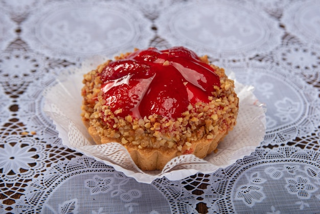 Aardbeiensnoepje met geplette kastanjes, in detail te zien op wit kanten tafelkleed, selectieve aandacht