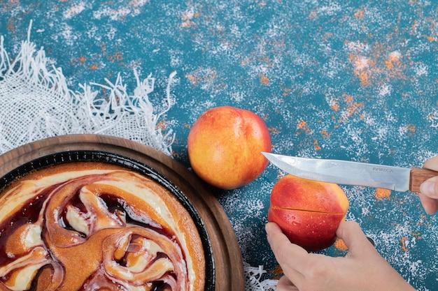 Aardbeienstrooptaart met gele perziken eromheen.