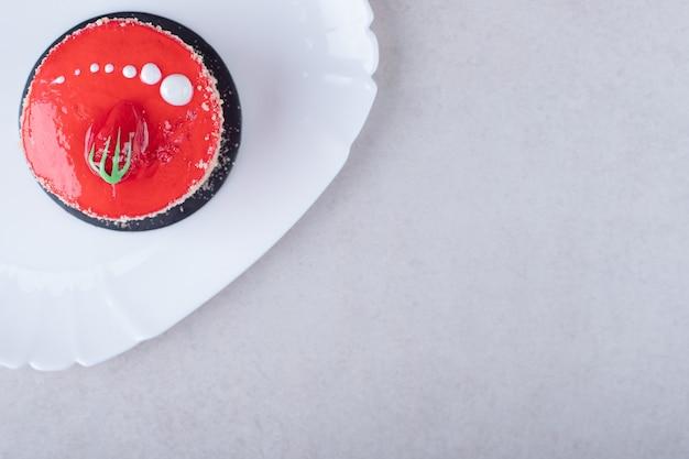 Aardbeientaart en chocolade gecoate wafeltjes op een bord op marmeren tafel.