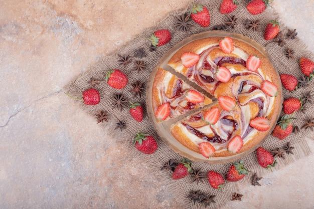 Aardbeientaart met rode siroop, fruit en anijsbloemen.