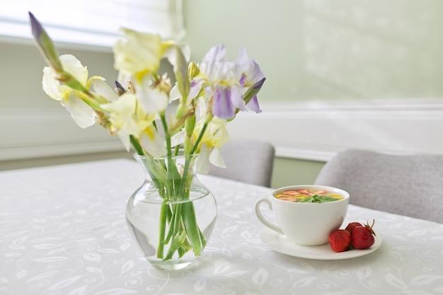 Aardbeienthee met munt-citroenbessen op tafel close-up. tafel bij het raam met vaas met irissen bloemen