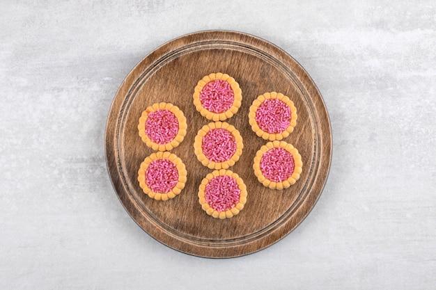 Aardbeigelei koekjes op een bord, op de marmeren tafel.