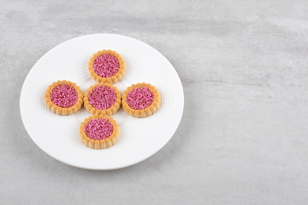 Aardbeigelei koekjes op een schaal, op het marmer.