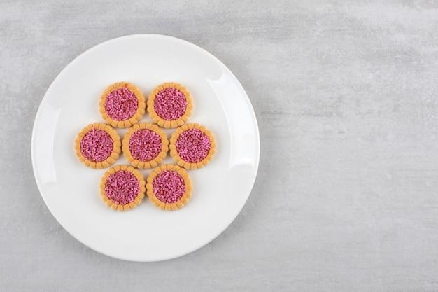 Aardbeigelei koekjes op een schotel, op de marmeren tafel.