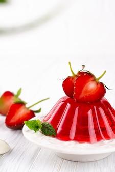 Aardbeigelei op witte plaat. zomer dessert met fruitgelei en verse aardbeien.