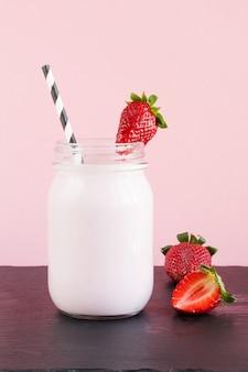 Aardbeimilkshake met bes in metselaarkruik op roze. detailopname. zomer drankje.