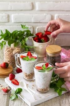 Aardbeiparfait met yoghurt, zelfgemaakte muesli en verse bessen op een stenen betonnen werkblad. kopieer ruimte.