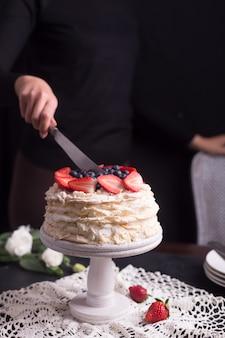 Aardbeipavlova-cake die door vrouw wordt verfraaid