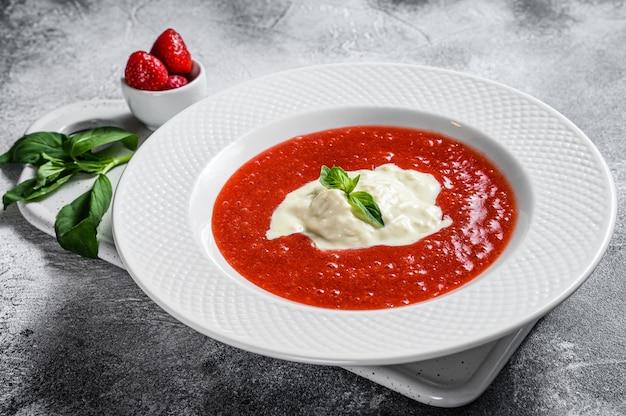 Aardbeipuree en buffelmozzarella. grijze muur. uitstekend italiaans dessert