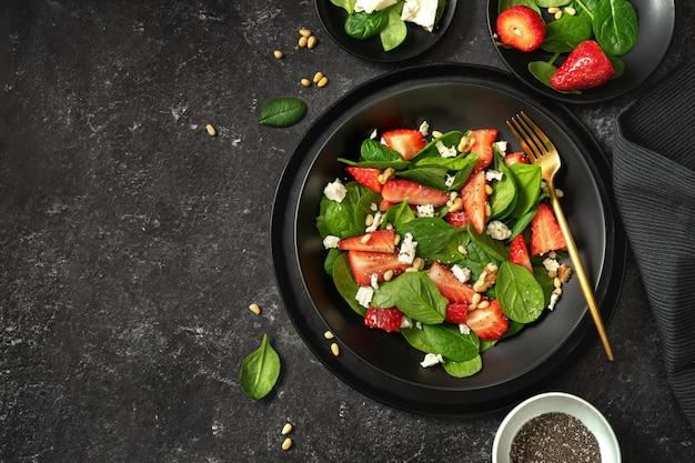 Aardbeisalade met spinazie, feta en noten op zwarte achtergrond