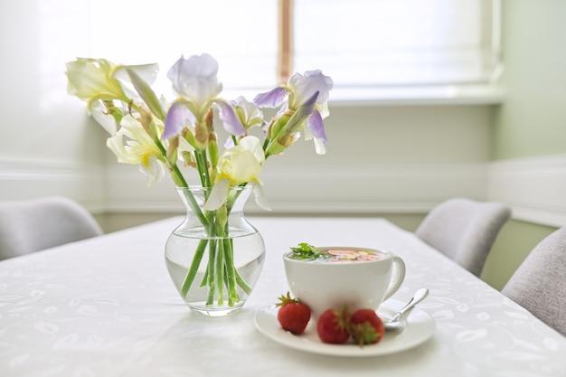 Aardbeithee met muntcitroenbessen op lijstclose-up. tafel bij het raam met vaas met irissenbloemen