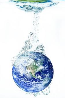 Aarde die in water op wit valt