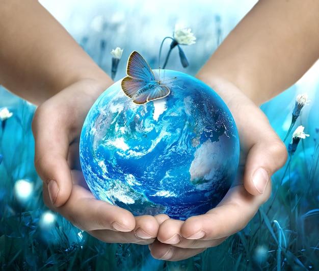 Aarde in handen. vlinder op wereldbol. ecologie concept. red van de aarde. wereld aarde dag. elementen van deze afbeelding zijn geleverd door nasa