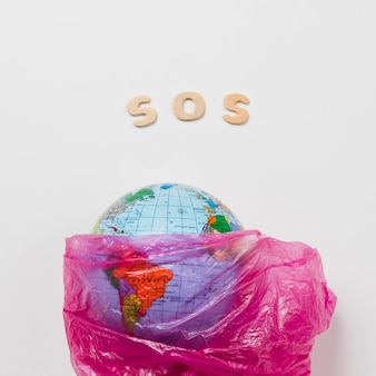 Aarde in plastic naast letters die sos zeggen