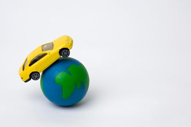 Aarde met miniatuurauto op wit