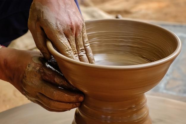 Aardewerk - bekwame natte handen van pottenbakker die de klei op pottenbakkerswiel vormt