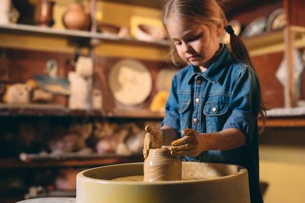 Aardewerk workshop. een klein meisje maakt een vaas met klei. kleimodellering