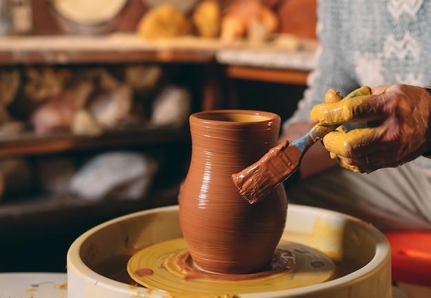 Aardewerk workshop. een senior man maakt een vaas met klei. kleimodellering