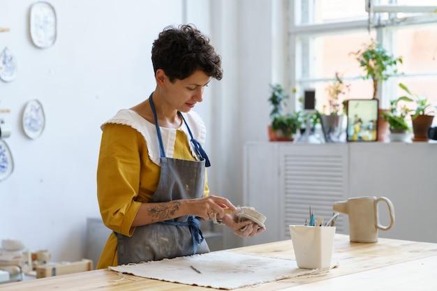 Aardewerk zakenvrouw kunstenaar maakt keramiek te koop en voor het onderwijzen van kunst voor studenten op workshop