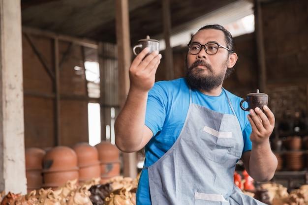 Aardewerkmaker die product bekijkt
