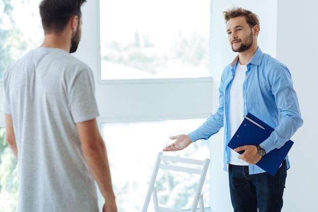 Aardige aangename knappe therapeut die een map met documenten vasthoudt en naar zijn patiënt kijkt terwijl hij hem uitnodigt om te gaan zitten