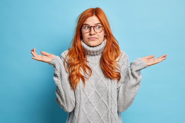 Aardige aantrekkelijke twijfelachtige vrouw haalt schouders op weet geen antwoord op moeilijke vraag geeft niet om je problemen staat onverschillig tegen blauwe muur heeft geen kennis toont onzeker gebaar Gratis Foto