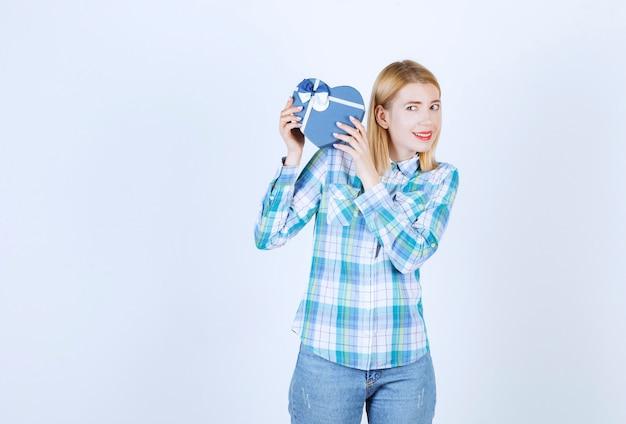 Aardige blonde vrouw verheft het blauwe geschenk in haar rechterzij voor de witte muur