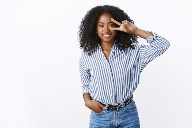 Aardige charmante glimlachende gelukkige jonge donkere meid met krullend haar die trendy gestreepte blouse-jeans draagt met disco vredesoverwinningsteken op oog grijnzend vrolijk poseren schattig geschoten witte muur