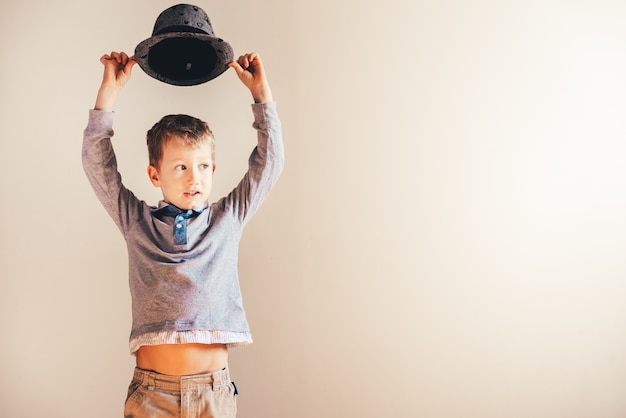 Aardige en knappe jongen met een elegante hoed, die op wit wordt geïsoleerd