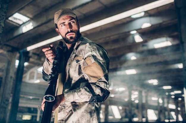 Aardige en zelfverzekerde jager staat en ziet er goed uit. hij heeft een geweer. ook houdt kerel draagbare radio in rechterhand. hij ziet er erg stil en voorzichtig uit.