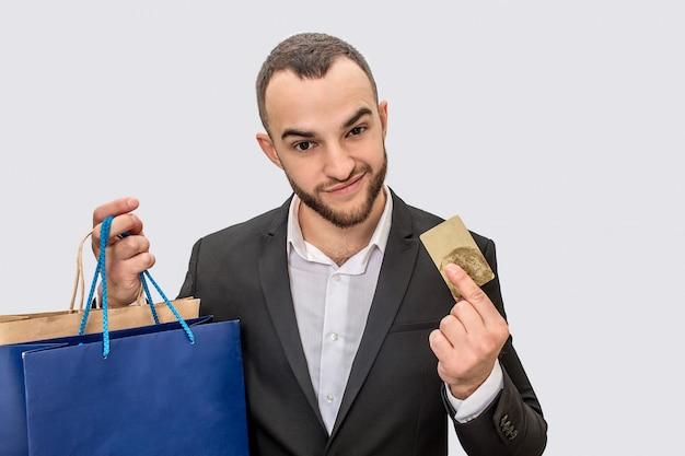 Aardige en zelfverzekerde jonge man in pak staat en toont creditcard. hij ziet er recht uit. jonge man heeft boodschappentassen in de hand.